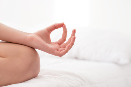 healthy woman: Home meditation. Close up shot of lotus pose and hand gesture accomplished by young healthy woman