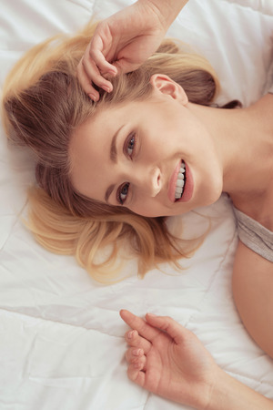 early morning: Joyful morning. Pretty young women is lying in bed and looking happy in the morning