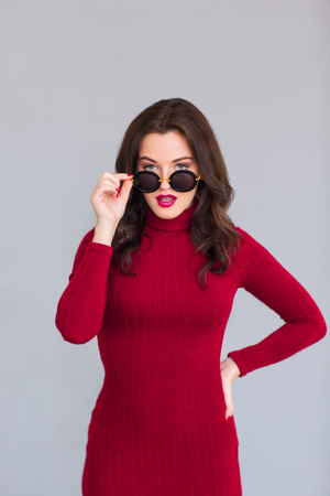 glance: Seductive glance. Charming pleasant woman wearing glasses and holding her hand on the waist line Stock Photo
