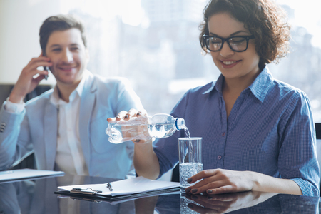 energy work: My source of energy. Pleasant positive woman pouring water in a glass  and sitting at the table with her colleague while resting after work Stock Photo