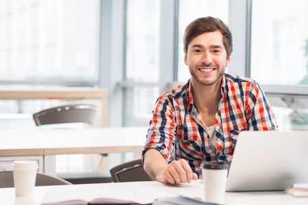 man shirt: Modern way of life. Positive handsome man sitting at the table  and working on the laptop while expressing positivity