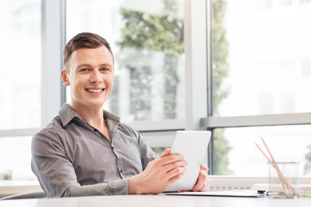 digital device: Work with inspiration. Pleasant handsome delighted man sitting at the table and holding tablet while smiling