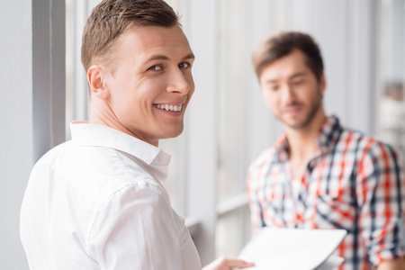 corporal: Stay positive. Delighted handsome man smiling and holding papers while standing near the window with his colleague