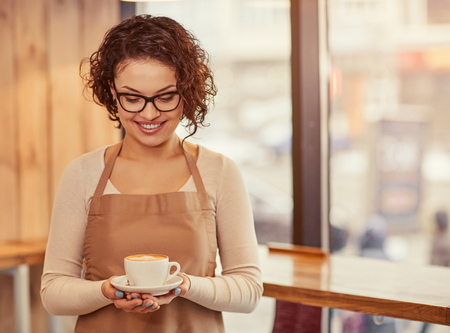 unforgettable: Unforgettable taste. Positive charming woman holding cup of coffee and expressing joy while standing in the cafe Stock Photo