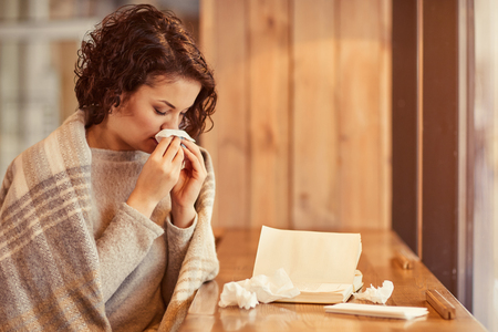 cheerless: Feel under the weather, Cheerless ill woman sitting at the table and using napkins while having snuffle