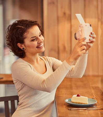 say cheese: Say cheese. Cheerful delighted charming woman holding photo camera and making selfie while sitting in the cafe Stock Photo
