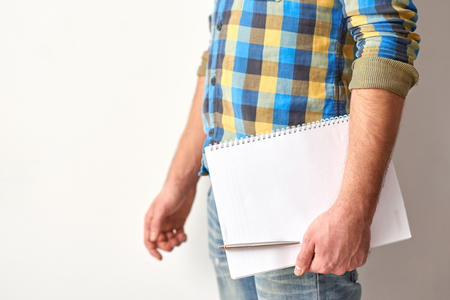 daily use item: Tools of intelligence. Cropped shot of man holding a notebook with pan isolated on white background.