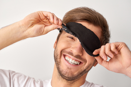 joyfully: Wide smile. Studio shot of young handsome man with blindfold looking and smiling joyfully.
