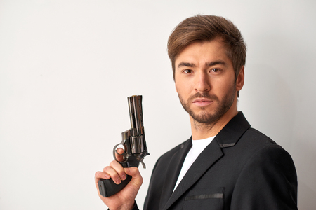 hostile: James Bond style. Close up shot of young handsome man holding a gun and looking hostile. Stock Photo