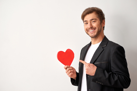 romantics: Love is best present. Shot of young beautiful man holding heart shape and looking happy.