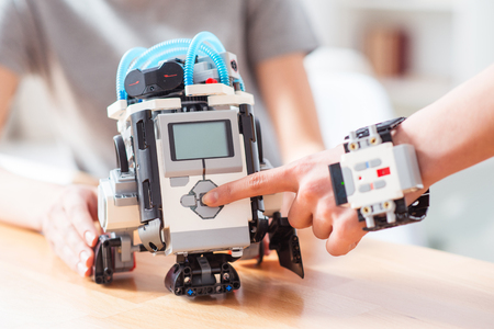 Switch on a new technology. Women is touching button on robot toy for start playing with