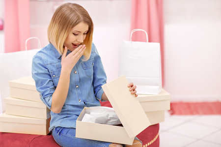 What a surprise. Pleasant positive attractive woman holding box with shoes and expressing surprise while shopping