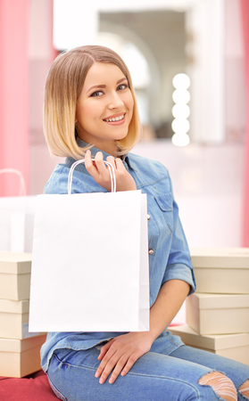 pouf: That is my finding. Cheerful content beautiful  woman sitting on the pouf and holding package while shopping