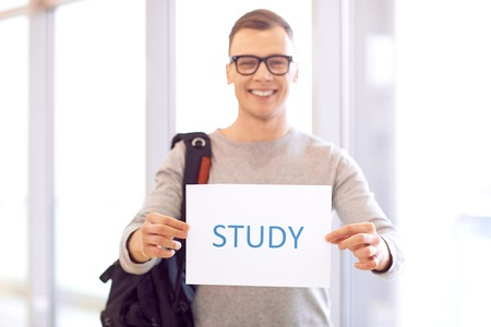 shit: Involved in study process. Shit of paper in hands of smart positive student holding it while standing near window