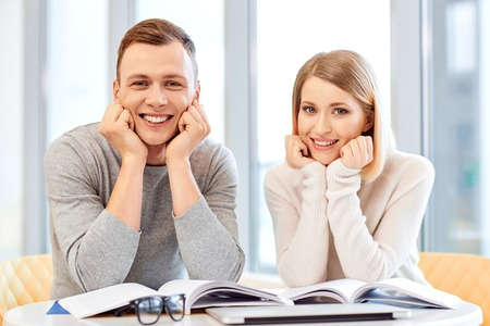 chins: Do it with pleasure. Delighted joyful students sitting at the table and holding hands under the chins while expressing positivity Stock Photo