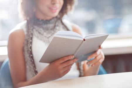 portadas de libros: Implicado en la trama. Hermosa chica agradable relajado sentado en la mesa y que sostiene el libro mientras descansa