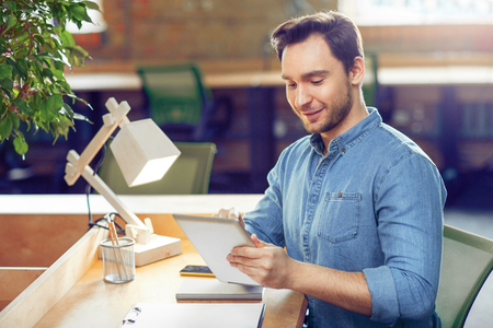 Soyez moderne. Agréable joyeux bel homme tenant la tablette et l'utiliser tout en étant assis à la table Banque d'images