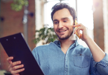 gladness: Busy world. Smiling positive handsome man holding folder and talking on mobile phone while expressing gladness Stock Photo