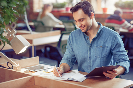 expressing joy: Involved in work. Pleasant handsome young man sitting at the table and making notes while expressing joy Stock Photo