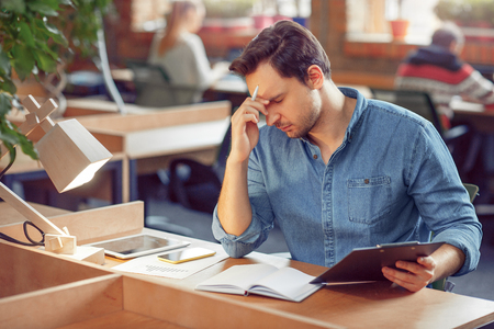 Viel Material zu tun. Müde schöner Mann am Tisch sitzen und arbeiten, während ein unangenehmes Gefühl Standard-Bild - 54497151