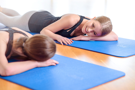 pleasant: Stay fit. Positive pleasant girls lying on the floor and smiling while  doing exercises Stock Photo