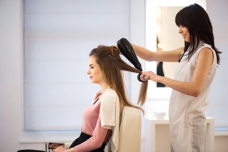 hairdresser: Best service Cheerful smiling professional hairdresser holding hairdryer   and drying hair of her client while working in the hairdressing salon