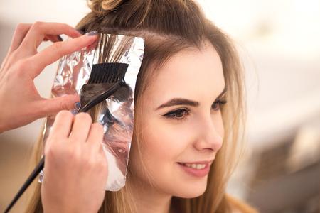 Machen Sie es richtig. Schöne charmante Frau im Friseursalon sitzen, während professionelle Friseur die Haare Färben Standard-Bild - 54628203