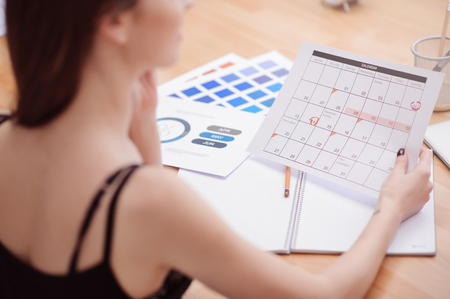 diligent: Diligent worker. Pleasant young woman sitting at the table and holding calendar while being involved in work