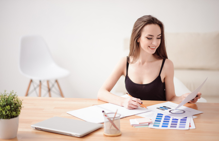vivacious: Much work to do. Cheerful vivacious charming girl sitting at the table and holding pencil while working with papers Stock Photo