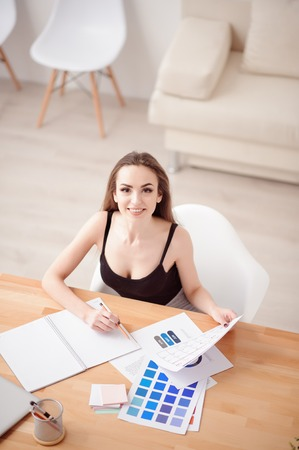 gladness: Do everything properly. Top view of delighted charming positive girl sitting at the table and expressing gladness while working with papers