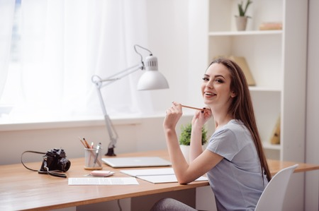 express positivity: Like what you do. Cheerful charming positive girl sitting at the table and holding pencil while expressing joy
