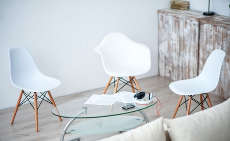 little table: Nice furnishing. View of nice light room with white chairs standing around the glass little table Stock Photo