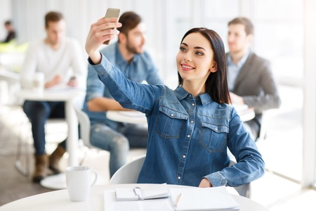 say cheese: Say cheese. Pleasant content smiling positive girl holding  cell phone and making photos while sitting at the table Stock Photo