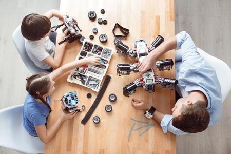 構築に関与します。陽気な楽しい父と彼の子供のテーブルに座って、レゴで遊ぶ 写真素材
