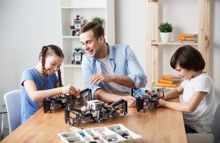 できます。彼の子供たちのテーブルに座って、ビルディング ブロックを構築する上で彼の娘を助ける陽気なの笑顔のコンテンツの父 写真素材