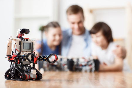 inventions: Helpful inventions. Selective focus of modern robot standing on the table while father and his children playing with building blocks in the background