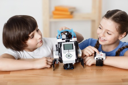 talking robot: Cheerful pretty delighted smiling children sitting at the table and playing with robot while resting