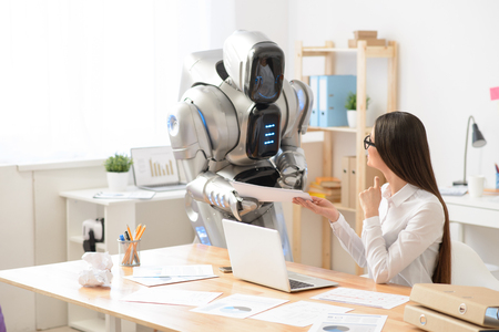 Cheerful content charming girl sitting at the table and smiling while the robot giving her papers Lizenzfreie Bilder