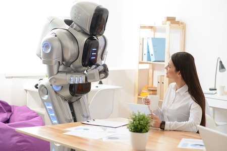 talking robot: Nice delighted woman sitting at the table and using tablet while talking with robot who is standing nearby