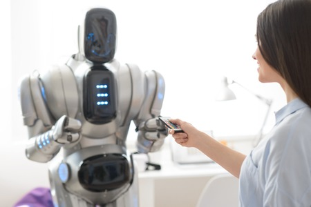 gladness: Smiling delighted beautiful girl holding remote control and expressing gladness while robot standing in the background