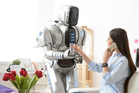 Smiling modern robot holding glass of water and giving it to nice charming woman who is sitting at the table and talking on cell phone