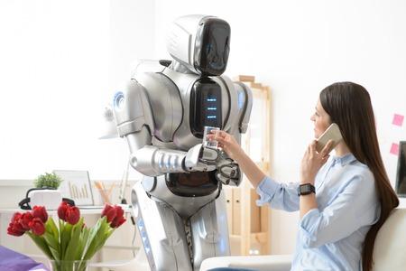 Sonriendo moderno robot sosteniendo el vaso de agua y le da a la mujer bonita con encanto que está sentado en la mesa y hablando por teléfono celular