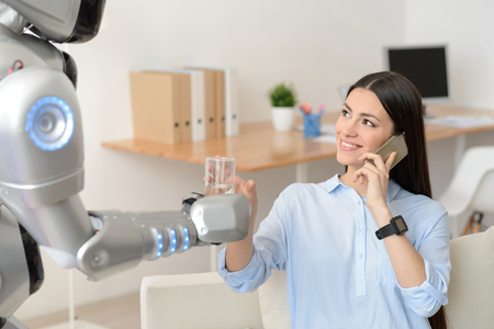 talking robot: Cheerful delighted beautiful girl sitting at the table and talking on cell phone while getting glass of water from the robot Stock Photo