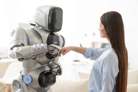 gladness: Pleasant positive girl and modern robot holding their hands in fists and holding them together while expressing gladness Stock Photo