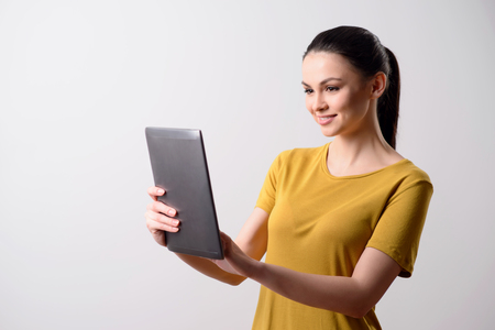 express positivity: Modern user. Cheerful positive delighted pretty girl holding tablet and expressing joy while standing isolated on grey background