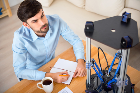 3d printer: Everything under control. Pleasant delighted bearded man sitting at the table and making notes while using 3d printer