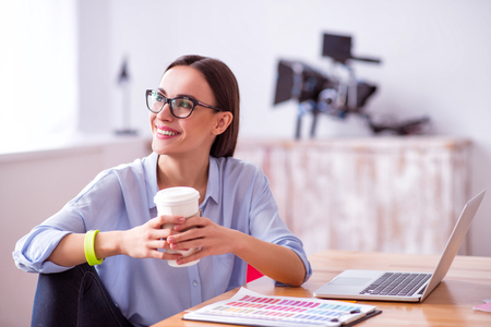 looking aside: Cheerful positive beautiful delighted woman sitting at the tale and drinking coffee while looking aside Stock Photo