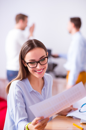 overjoyed: Cheerful overjoyed smiling beautiful woman sitting at the table and smiling while working with the papers Stock Photo