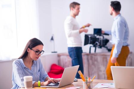 diligente: Agradable mujer concentra diligente sentado en la mesa y trabajar en la computadora portátil mientras que sus colegas de pie en el fondo