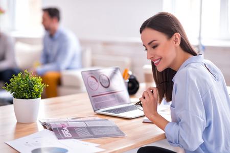 Bella ragazza sorridente allegra che si siede al tavolo e che legge rivista mentre per mezzo del computer portatile